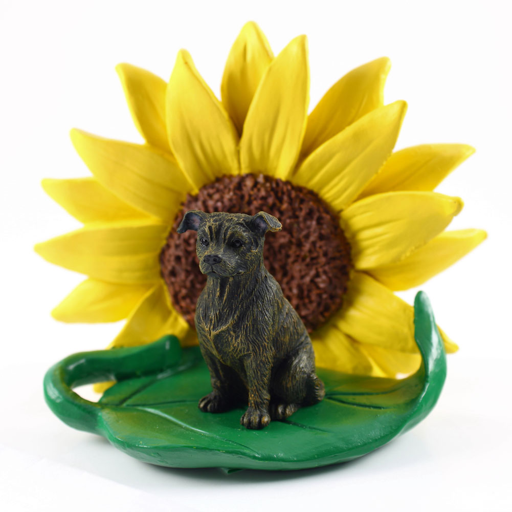 Staffordshire Bull Terrier Figurine Sitting on a Green Leaf in Front of a Yellow Sunflower