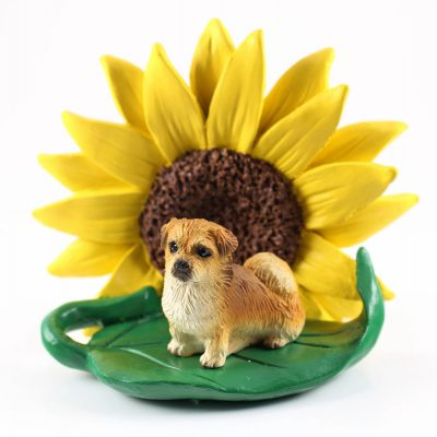 Tibetan Spaniel Figurine Sitting on a Green Leaf in Front of a Yellow Sunflower