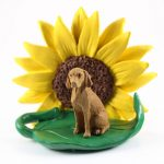 Vizsla Figurine Sitting on a Green Leaf in Front of a Yellow Sunflower